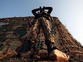 """Ein indischer Soldat beobachtet an der """"Line of Control"""" die Umgebung."""