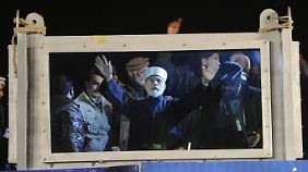 Hinter kugelsicherem Glas ruft Qadri seine Landsleute zur Revolution gegen die Regierung auf.