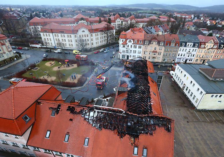 Bautzen am Morgen nach der Feuernacht: Noch immer steigt Rauch aus dem zerstörten Dachstuhl eines ehemaligen Hotels auf.