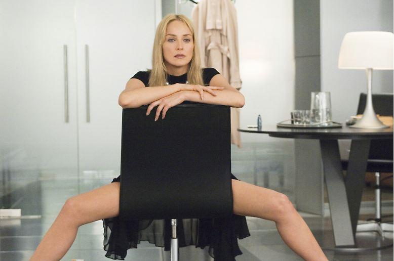 Sharon Stone breitbeinig auf einem Stuhl ... Das weckt Erinnerungen, oder? Eine ähnliche Pose machte sie (wenn auch ohne Stuhllehne und mit einem weitaus tieferen Einblick) ...