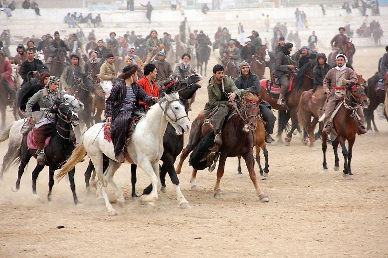Die Reiter stürmen heran, in einer Staubwolke, die die Stadt hinter ihnen verschwimmen lässt.